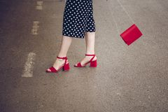 圆点culottes和红色高跟鞋的时髦的妇女穿上鞋子拿着一个红色钱包和穿过路 街道样式时尚 免版税库存图片