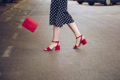圆点culottes和红色高跟鞋的时髦的妇女穿上鞋子拿着一个红色钱包和穿过路 街道样式时尚 库存图片