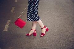 圆点culottes和红色高跟鞋的时髦的妇女穿上鞋子拿着一个红色钱包和穿过路 街道样式时尚 免版税库存照片