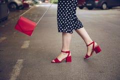 圆点culottes和红色高跟鞋的时髦的妇女穿上鞋子拿着一个红色钱包和穿过路 街道样式时尚 图库摄影