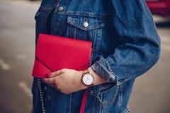 圆点culottes的时髦的妇女和拿着一个红色钱包和佩带玫瑰金手表的牛仔布夹克 库存图片
