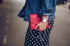 圆点culottes的时髦的妇女和拿着一个红色钱包和佩带玫瑰金手表的牛仔布夹克 免版税图库摄影