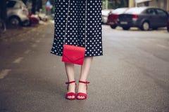 圆点culottes的时髦的妇女和拿着一个红色钱包和佩带玫瑰金手表的牛仔布夹克 免版税库存图片