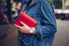 圆点culottes的时髦的妇女和拿着一个红色钱包和佩带玫瑰金手表的牛仔布夹克 库存照片
