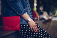 圆点culottes的时髦的妇女和拿着一个红色钱包和佩带玫瑰金手表的牛仔布夹克 免版税库存照片