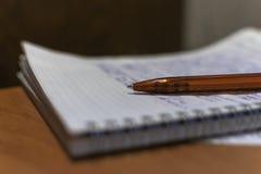 圆珠笔和笔记本在桌面上 免版税库存图片
