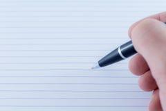 黑圆珠笔文字笔在手中 免版税库存照片