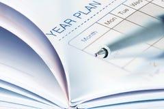 圆珠笔的选择聚焦在被打开的被排行的日志书的与 库存图片