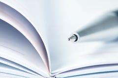 圆珠笔选择聚焦在被打开的被排行的日志书的 免版税库存照片