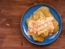 圆白菜卷,在蓝色板材的白菜卷在木背景平的视图 免版税库存图片