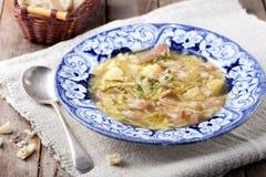 圆白菜汤用烟肉,土豆,肉,陶瓷板材,面包 图库摄影