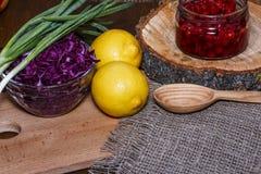 圆白菜红色,柠檬,在一个委员会的葱绿色有粗麻布的 免版税库存照片