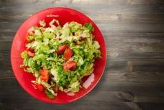 圆白菜蕃茄沙拉在一块板材的在木背景 免版税库存图片