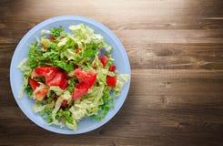 圆白菜蕃茄沙拉在一块板材的在木背景 图库摄影