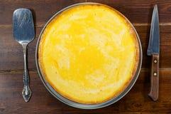 圆的与小铲和刀子的乳酪蛋糕顶视图 免版税库存照片