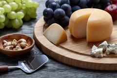 圆的乳酪用在木backround的葡萄 库存照片