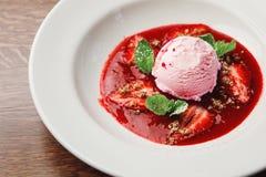 圆的冰淇凌瓢桃红色的美好和开胃水平的特写镜头图象在用红色调味汁补充的板材的 库存图片