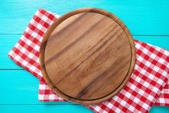 圆的切板和红色格子花呢披肩桌布框架  在咖啡馆的蓝色木背景 顶视图 宏指令 免版税库存图片