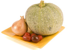 圆的夏南瓜、葱和小的蕃茄在板材 库存图片