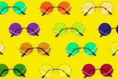 圆的多彩多姿的太阳镜的汇集 在黄色背景的夏天样式 时尚汇集 热带旅行的太阳镜 库存照片