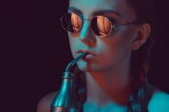 圆的太阳镜的女孩喝从水瓶的苏打有秸杆的 免版税库存照片