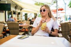 圆的太阳镜的年轻美女有在获得的咖啡馆大阳台的鸡尾酒的乐趣 库存照片