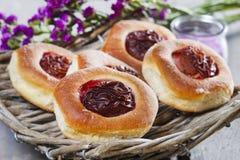 圆的小圆面包用在木桌上的李子 库存图片