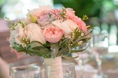 圆的新娘花束以淡色牡丹和玫瑰为特色的,鞋带和绿叶,在一个透明花瓶的集合 库存照片
