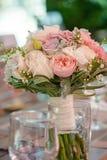 圆的新娘花束以淡色牡丹和玫瑰为特色的,鞋带和绿叶,在一张桌上的集合,与选择聚焦 库存图片
