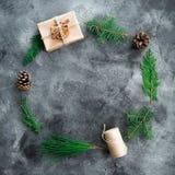 圆的框架由圣诞节礼物盒、冬天树枝和杉木锥体做成在黑暗的桌 构成新年度 平的位置 顶视图 图库摄影