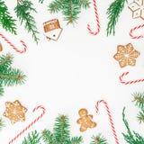 圆的框架由姜饼曲奇饼、冬天树和棒棒糖制成在白色背景 平的位置 顶视图 圣诞节新年度 免版税图库摄影