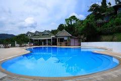 圆的游泳池、太阳懒人在庭院旁边和塔 库存图片