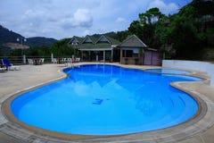 圆的游泳池、太阳懒人在庭院旁边和大厦 免版税图库摄影