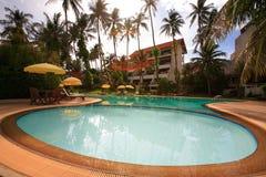 圆的游泳池、太阳懒人在庭院旁边和大厦 免版税库存图片