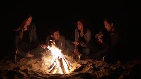 圆的照相机运动:后坐由篝火的多种族小组年轻男孩和女孩在夜和唱歌歌曲 股票视频