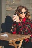 圆的玻璃的年轻美丽的妇女喝咖啡的 免版税库存图片