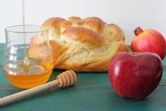 圆的甜鸡蛋面包、蜂蜜瓶子、红色苹果和石榴在t 免版税库存图片