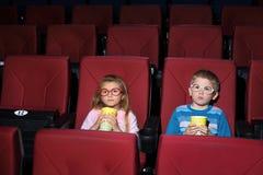 戴圆的眼镜吃玉米花的小男孩和女孩 免版税图库摄影