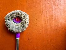 圆的笤帚布料拖把转台式紫罗兰色把柄在橙色墙壁倾斜了作为与空间的背景文本的 免版税库存图片