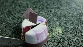 圆的紫罗兰色奶油甜点蛋糕由刀子切成了两半 股票视频