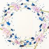 圆的花卉框架蓝色和桃红色花和卡片在白色背景 平的位置,顶视图 博克、社会媒介或者网站backgroun 免版税库存照片