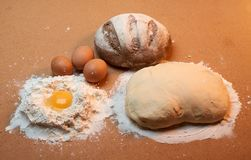 圆的面包、三个鸡蛋、面团和面粉围拢的蛋黄 免版税库存图片