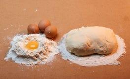 圆的面包、三个鸡蛋、面团和面粉围拢的蛋黄 免版税库存照片