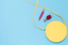 圆的黄色钱包,红色指甲油,在淡色蓝色背景的红色唇膏 免版税库存图片