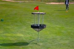 圆盘高尔夫球在草地的frolf篮子 库存图片