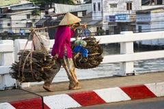 圆锥形亚洲帽子运载的木头的赤足越南成熟妇女在2012年2月13日的拥挤的街在我的Tho,越南 库存图片