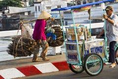 圆锥形亚洲帽子运载的木头的赤足越南成熟妇女在2012年2月13日的拥挤的街在我的Tho,越南 免版税库存图片