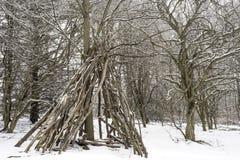 圆锥形帐蓬contructed在日志外面,并且分支在一个冬天环境美化 图库摄影
