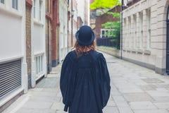 圆顶硬礼帽和毕业褂子的妇女 库存照片
