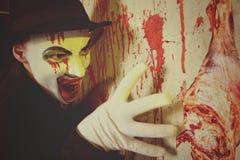 戴圆顶硬礼帽的可怕邪恶的小丑 库存照片